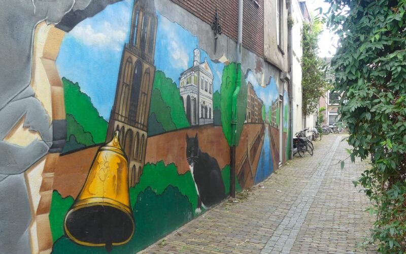 Afbeelding van muurschildering met daarin verwerkt een kerktoren en een koperen bel.