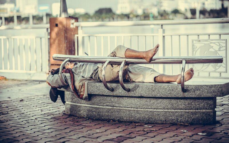 Jong volwassenen die dakloos is en op een bankje ligt